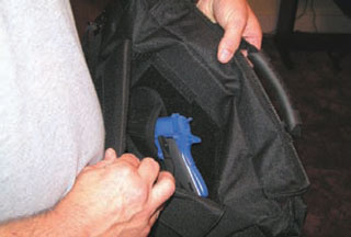 Uncle Mike's concealed carry briefcase has a discreet, but very accessible holster built right in. In this case, a Rings Blue Gun stands out against the black nylon and it is also a good idea when you are setting up the holster and practicing your draw. (Photo by Adam Michalowski.)