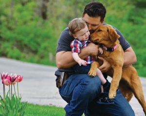A man wearing a small pistol i an OWB holster squats down to hug his young son and a lab puppy. The setting is a front yard near a flower garden.
