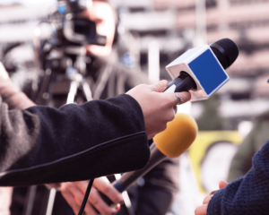 Close-up photo of reporters holding microphones in a group during a press briefing.