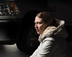 Dramatically lit photo of a white woman in a white winter parka, kneeling beside the front bumper and driver-side wheel of an SUV. Her face shows great concern and perhaps surprise.