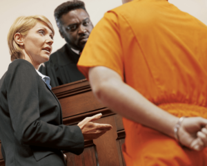 A white male prisoner in an orange prison jumpsuit with his hand cuffed behind his back stands before a white female attorney and an African-American male judge behind his bench.