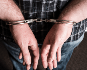 A white male in a blue plaid shirt and denim jeans has his wrists cuffed with silver metal handcuffs behind his back.