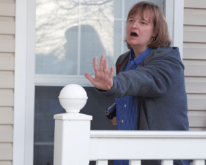 A woman in a gray hoodie and blue and white striped shirt holds her left hand forward, palm out, as if to ward off an attacker. She has a pistol held close to her body in her right hand and her mouth is open as if shouting verbal commands. The setting is the front porch of a residence, near a window.