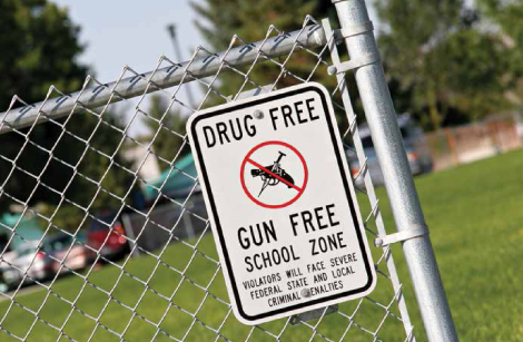 Gun free zone sign posted on a fence