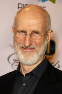 Actor James Cromwell in a black shirt and oval glasses, smiling
