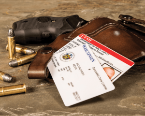 A black .38 snub-nosed revolver encased in a brown leather holster and lying on a countertop. Two concealed carry permits - one for Wisconsin and one for Utah - are stacked atop the holster.
