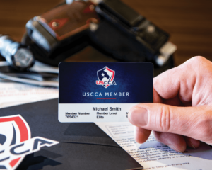 A Caucasian hand holding a blue USCCA Membership card. On the tabletop below is the folder of the USCCA welcome package as well as a holstered pistol.