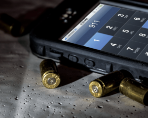 A black smartphone's keypad has been used to dial 911. The phone lies next to three spent 9mm brass casings.