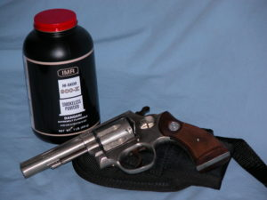 A revolver lying on a black nylon holster before a canister of HI-SKOR 800X smokeless powder