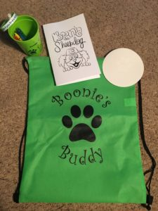 Bright green Boonie's Buddy backpack along with a sticker, coloring book and crayons