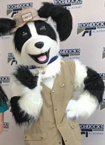 Boonie the Sheepdog mascot wering a khaki vest and khaki hat, osing in front of a white wall bearing the logo for Boondocks Firearms Training Academy (BFTA)