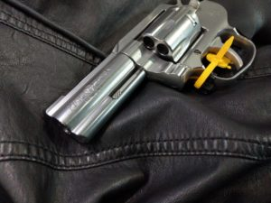 Silver Colt King Cobra .357 Magnum revolver with a yellow triger safety device resting on a black leather jacket