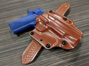 Brown leather DeSantis Variable outside-the-waistband (OWB) holster containing a blue practice pistol