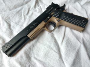 Remington 1911-style semi-automatic handgun in two-tone black and Flat Dark Earth (FDE) lying on a wrinkled white cloth background.
