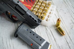 A black .45-caliber semi-automatic handgun rests next to an empty black steel seven-shot single-stack magazine and an open box of .45 ACP ammunition with two fat little ball rounds removed from the package.