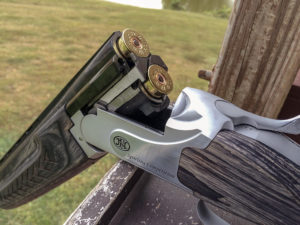 A silver and ash over-and-under double-barrel shotgun rests with its breech broken open, revealing two unfired 12-gauge shells