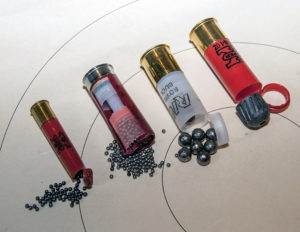 A .410 shotgun shell and three 12-gauge shells with brass bases and plastic casings have been cut open at the muzzle end to reveal the variety of shot and slugs each contains.