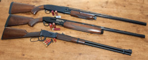 Three shotguns, a lever-action, semi-automatic, and pump-action, all with blued metal and wooden stocks and foreends, lying on a rustic wooden background amidst a variety of red and black .410 and 12-gauge shotshells