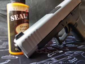 A two-tone silver and black Glock 48 9mm semi-automatic pistol propped against a yellow bottle of SEAL 1 non-toxic gun cleaning solution