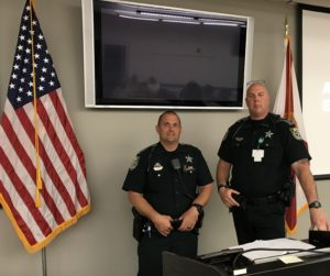 Two uniformed Hernando County Florida deputies standing in a classroom next to an American flag and a black CCTV monitor