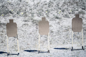 Three cardboard silhouette targets on wooden stands downrange at an outdoor shooting range on a bright, suny day. he argets are peppered with bullet holes in the chest and head areas. A dirt berm is covered with scrub grass in the background.