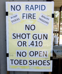 Handmade vertical yellow sign featuring areas plastered with cut white paper and large black letters. The ad hoc sign reads NO RAPID FIRE, BUMP STOCKS, BINARY TRIGGERS, NO SHOT GUN OR .410 NO OPEN TOED SHOES