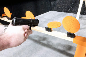 A white male with pale hands grips a black semiautomatic pistol while aiming the muzzle at an orange disc polymer target in an indoor range with black walls and backdrop