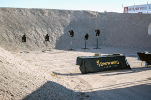 A large berm surrounds the back and sides of an outdoor range. The firing line benches are covered with black tablecloths bearing yellow Browning Ammunition logos. Five black silhouette targets stand on wooden frames downrange.