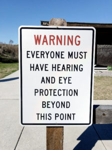 Vertical white metal sign with a thin black border attached to a wooden post at an outdoor shooting range. The sign has WARNING in big red letters followed by EVERYONE MUST HAVE HEARING AND EYE PROTECTION BEYOND THIS POINT in capital black letters.