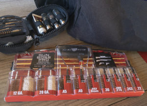 GUN BOSS PRO universal firearm cleaning kit and a black nylon pouch full of gun cleaning brushes next to a black range bag on a background of unfinished wooden planks