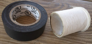 A roll of black plastic electrician's tape and a roll of white athletic tape lying beside each other on a background of unfinished lumber planks