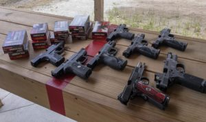 A variety of 9mm and .45-caliber semi-automatic handguns lying with their slides locked open and their muzzles pointed downrange on the wooden bench of an outdoor shooting range. Several boxes of American Eagle brand ammunition also sit on the shooting bench.