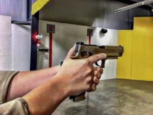 White male hands holding a full-sized semi-automatic pistol in FDE. The muzzle is pointed downrange at an indoor shooting range with yellow containment walls.
