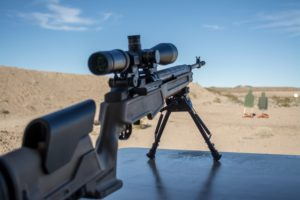 A rifle with a scope and marksman's stock rests on a bipod on a shooting bench at an outdoor range with beautiful blue skies, an earthen berm and two silhouette targets downrange