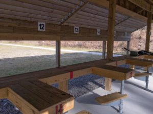 Outdoor shooting range lanes numbered 12, 13, 14, 15 and 16 featuring heavy wooden benches, seats , beams and a roof