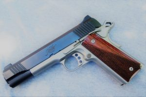 Shiny Kimber 1911-style handgun with wooden grips and an aftermarket triger