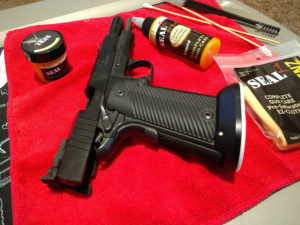Black 1911-style handgun sitting with its slide locked open on a red gun cleaning pad