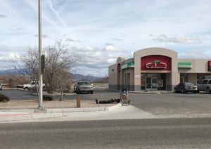 A homeless person lies beside a shopping cart near a street and a Papa John's parking lot in New Mexico