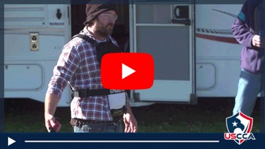 Video still of a role player in a stress vest brandishing a red practice knife with a white RV in the background