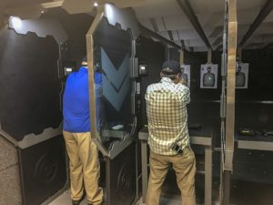 Two men, one in khaki pants and a blue shirt and the other in khaki pants and a plaid shirt, stand in their firing lanes and aim their firearms downrange. One is using a green laser mounted on his pistol to illuminate his white paper target.