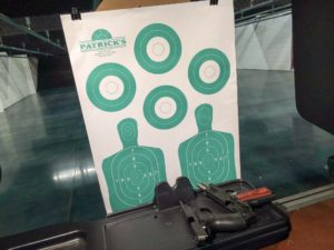 White paper target from Patrick's in Garden City, GA – featuring two human silhouettes with vitals marked and four circular targets in teal ink.