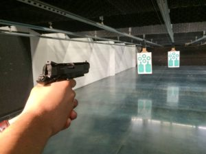 White man aiming a cocked 1911-style semi-automatic pistol down an indoor shooting range. Two blue-on-white paper targets hand from the automated target system.