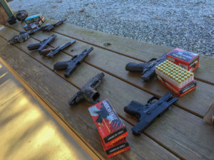 A variety of semi-automatic pistols and a revolver all sitting on a wooden plank shooting bench with their muzzles pointed downrange. A few red boxes of American eagle brand ammunition are dispersed among the handguns