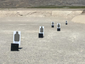 Targets set up at various distances on an utdoor shooting range on a sunny day, with a large dirt berm in the background