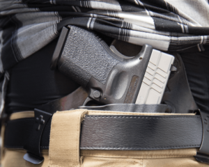 A two-tone Springfield Armory semi-automatic pistol concealed in a Crossbreed brand IWB holster. The stocks ride high above the wearer's black leather belt and a gray plaid shirt has been pulled away to reveal the gun.