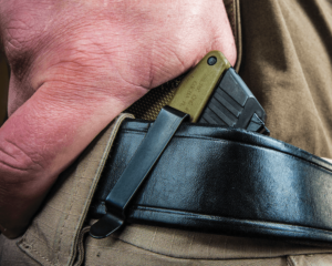 Close-up of a man's right hand gripping a green and black semi-automatic pistol that has been concealed in an inside-the-waistband (IWB) holster. The only visible portion of the holster is a black metal clip where it attaches to the man's black leather belt.