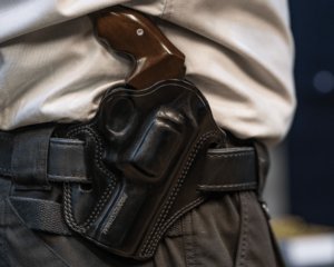 A revolver with wooden grips encased in a black leather Outside the Waistband (OWB) holster. The carrier is wearing a black belt, gray dress pants and a white dress shirt.