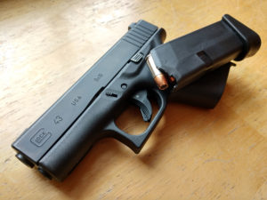Black compact GLOCK G43 9mm semi-automatic concealed carry pistol lying on its side under a black factory OEM 6-round magazine filled with Hornady Critical Defense 9mm 115-grain FTX nickel and copper personal defense ammunition.