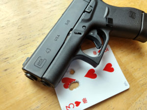 Black GLOCK G43 9mm semi-automatic concealed carry 9mm pistol lying on a wooden background atop a three of hearts playing card which shows a tight group of bullet holes with one flyer.