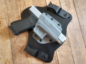 A two-tone black and silver Glock G48 holstered inside a gray Kydex and black leather hybrid CrossBreed SuperTuck inside-the-waistband (IWB) holster that is lying on a rustic hardwood floor.